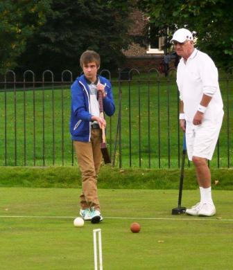 York Croquet Club's youngest player considers the next shot with a seasoned Scotland international player at the Yorkshire Tournament