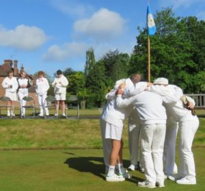 Four of the England Ladies croquet team look on with amusement as Yorkshire get into a 'team huddle' complete with Yorkshire flag and ferret